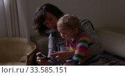 Купить «Caucasian woman with baby looking smartphone at home», видеоролик № 33585151, снято 12 апреля 2019 г. (c) Wavebreak Media / Фотобанк Лори