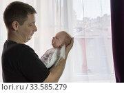 Молодой отец нежно держит младенца на руках. Маленькая девочка капризничает. Стоковое фото, фотограф Наталья Гармашева / Фотобанк Лори