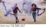 Dancers in an empty warehouse holding smoke grenade. Стоковое видео, агентство Wavebreak Media / Фотобанк Лори