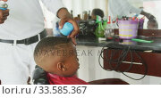Купить «African man making finishes at African boy hair», видеоролик № 33585367, снято 19 сентября 2019 г. (c) Wavebreak Media / Фотобанк Лори