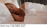 Caucasian woman resting in bed in hotel room. Стоковое видео, агентство Wavebreak Media / Фотобанк Лори