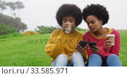 Two mixed race women drinking coffee and listening music in park. Стоковое видео, агентство Wavebreak Media / Фотобанк Лори