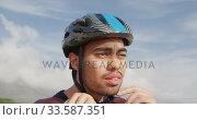 Young man putting on his helmet. Стоковое видео, агентство Wavebreak Media / Фотобанк Лори
