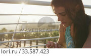 Купить «Young woman looking at her watch», видеоролик № 33587423, снято 26 июня 2019 г. (c) Wavebreak Media / Фотобанк Лори