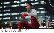 Купить «Young woman putting on ribbon», видеоролик № 33587447, снято 26 июня 2019 г. (c) Wavebreak Media / Фотобанк Лори