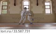 Купить «Fencer athletes during a fencing training in a gym», видеоролик № 33587731, снято 16 ноября 2019 г. (c) Wavebreak Media / Фотобанк Лори
