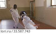 Купить «Fencer athletes during a fencing training in a gym», видеоролик № 33587743, снято 16 ноября 2019 г. (c) Wavebreak Media / Фотобанк Лори