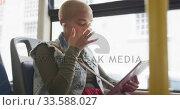 Купить «Mixed race woman taking the bus and using a digital table», видеоролик № 33588027, снято 10 января 2020 г. (c) Wavebreak Media / Фотобанк Лори