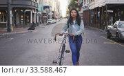 Купить «Mixed race woman walking next to her bike on the street», видеоролик № 33588467, снято 23 февраля 2020 г. (c) Wavebreak Media / Фотобанк Лори