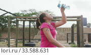 Caucasian woman pouring water on her face at bootcamp. Стоковое видео, агентство Wavebreak Media / Фотобанк Лори