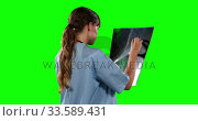 Side view of female doctor looking at X-ray with green screen. Стоковое видео, агентство Wavebreak Media / Фотобанк Лори