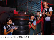 Smiling young friends playing laser tag game with colored laser guns near tires in labyrinth. Стоковое фото, фотограф Яков Филимонов / Фотобанк Лори