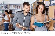 Купить «Young man and girl students studying in library, reading books», фото № 33606275, снято 26 июля 2018 г. (c) Яков Филимонов / Фотобанк Лори