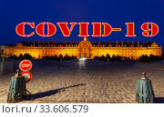 Coronavirus in Paris, France. Covid-19 sign on a blurred background. Concept of COVID pandemic and travel in Europe. Les Invalides (The National Residence of the Invalids) at night. Стоковое фото, фотограф Владимир Журавлев / Фотобанк Лори