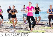 Sporty people practicing yoga on beach. Стоковое фото, фотограф Яков Филимонов / Фотобанк Лори