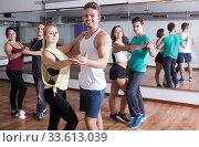 Group of positive adults dancing salsa together. Стоковое фото, фотограф Яков Филимонов / Фотобанк Лори