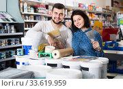Купить «loving couple demonstrating tools for house renovating in paint store», фото № 33619959, снято 9 марта 2017 г. (c) Яков Филимонов / Фотобанк Лори