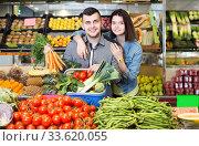 Купить «Young satisfied couple choosing vegetables in grocery shop», фото № 33620055, снято 18 марта 2017 г. (c) Яков Филимонов / Фотобанк Лори