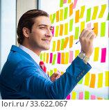 Купить «Young handsome employee with many conflicting priorities», фото № 33622067, снято 15 августа 2018 г. (c) Elnur / Фотобанк Лори