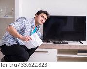 Купить «Man trying to fix broken tv», фото № 33622823, снято 9 марта 2018 г. (c) Elnur / Фотобанк Лори