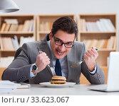 Hungry funny businessman eating junk food sandwich. Стоковое фото, фотограф Elnur / Фотобанк Лори
