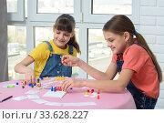 Купить «Две счастливые девочки проводят домашний досуг играя в игры», фото № 33628227, снято 5 апреля 2020 г. (c) Иванов Алексей / Фотобанк Лори