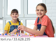 Купить «Две счастливые девочки играют в настольную игру и посмотрели в кадр», фото № 33628235, снято 5 апреля 2020 г. (c) Иванов Алексей / Фотобанк Лори