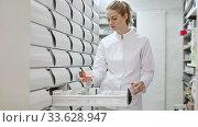 Young glad female customer searching for reliable drug in pharmacy. Стоковое видео, видеограф Яков Филимонов / Фотобанк Лори