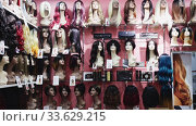Купить «Various natural hair wigs for sale on mannequins on shelves of specialized store», видеоролик № 33629215, снято 24 февраля 2020 г. (c) Яков Филимонов / Фотобанк Лори