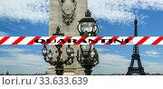 Coronavirus in Paris, France. Quarantine sign. Concept of COVID pandemic and travel in Europe. The Alexander III bridge and Eiffel Tower. Стоковое фото, фотограф Владимир Журавлев / Фотобанк Лори