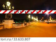 Coronavirus in Paris, France. Covid-19 sign. Concept of COVID pandemic and travel in Europe. The Alexander III bridge at night. Стоковое фото, фотограф Владимир Журавлев / Фотобанк Лори