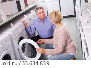 Купить «Mature smiling couple choosing home washing machine», фото № 33634839, снято 30 июня 2020 г. (c) Яков Филимонов / Фотобанк Лори