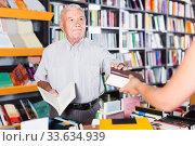Купить «Mature man is purchasing book in bookstore», фото № 33634939, снято 28 июня 2017 г. (c) Яков Филимонов / Фотобанк Лори