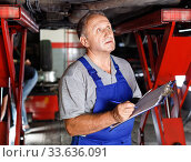 Skilled mature male mechanic taking notes in notebook about car repair at auto service. Стоковое фото, фотограф Яков Филимонов / Фотобанк Лори
