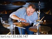 Купить «Adult man is choosing drum kit in music store.», фото № 33636147, снято 18 сентября 2017 г. (c) Яков Филимонов / Фотобанк Лори