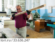 Купить «Positive craftsman working on a thicknessing machine», фото № 33636247, снято 13 июля 2020 г. (c) Яков Филимонов / Фотобанк Лори