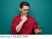 Купить «Portrait of a handsome young man in glasses with smartphone», фото № 33637059, снято 10 марта 2019 г. (c) Pavel Biryukov / Фотобанк Лори