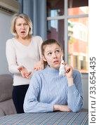 Mature mother and adult daughter quarrelling in domestic interior. Стоковое фото, фотограф Яков Филимонов / Фотобанк Лори