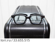 An eyeglasses is on top of black pc tower case with usb connection sockets, power and reset buttons, close up view. Стоковое фото, фотограф Кекяляйнен Андрей / Фотобанк Лори