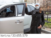 Attractive adult woman wearing black coat and one use face mask standing next to her car with opened door. Стоковое фото, фотограф Кекяляйнен Андрей / Фотобанк Лори