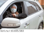 Купить «Attractive European woman wearing medical mask sits inside her car on driver seat», фото № 33655583, снято 24 апреля 2020 г. (c) Кекяляйнен Андрей / Фотобанк Лори