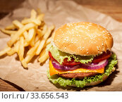 Купить «Fresh delicious burger with cheese, tomato, onion, lettuce and french fries on brown paper on wooden table», фото № 33656543, снято 5 июля 2020 г. (c) age Fotostock / Фотобанк Лори