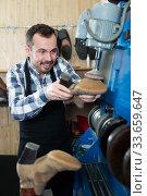 Man worker repairing shoes in repair workshop. Стоковое фото, фотограф Яков Филимонов / Фотобанк Лори