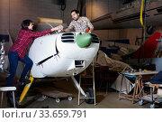 Купить «Two young mechanics, man and woman, repairing light sport plane in workshop», фото № 33659791, снято 4 марта 2019 г. (c) Яков Филимонов / Фотобанк Лори