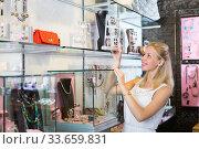 Young smiling female customer picking earrings. Стоковое фото, фотограф Яков Филимонов / Фотобанк Лори