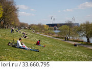 Germany, Bremen - People enjoy the sun at the Osterdeich on the Weser, in the back the Weserstadion. Редакционное фото, агентство Caro Photoagency / Фотобанк Лори