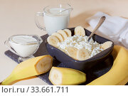 Food, balanced nutrition, healthy diet protein breakfast made from dairy and fruit. Fresh calcium source of homemade cottage cheese in a bowl with sliced banana milk cream sour cream and yogurt. Стоковое фото, фотограф Светлана Евграфова / Фотобанк Лори