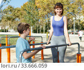 Купить «Family exercising on parallel bars outdoors», фото № 33666059, снято 11 ноября 2018 г. (c) Яков Филимонов / Фотобанк Лори