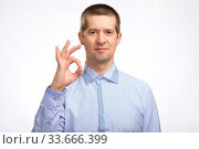 Купить «successful happy man shows the gesture OK with one hand, in a blue light casual shirt staring at the camera. Isolated», фото № 33666399, снято 22 апреля 2020 г. (c) Владимир Арсентьев / Фотобанк Лори