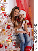 happy mom and daughter sit in a beautifully decorated room near a Christmas tree. Стоковое фото, фотограф Иванов Алексей / Фотобанк Лори